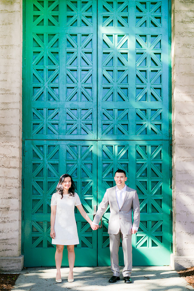 holding hand standing in front of green door